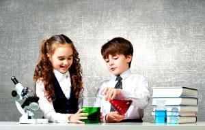un garçon et une fille réalisent ensemble des experiences scientifiques dans le cadre d'un établissement scolaire