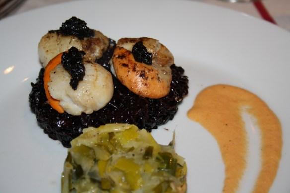 St Jacques purée d'ail noir sur risotto de riz noir venere sauce corail et fondue de poireaux