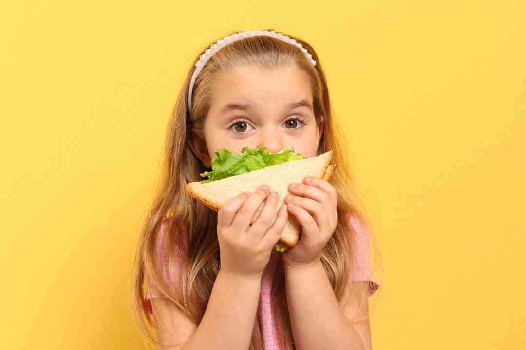 Photo petite fille qui mange un sandwich