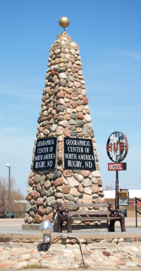 The Rugby Geographical Center of North America monument juxtaposed with the HUB Motel sign in Rugby, ND