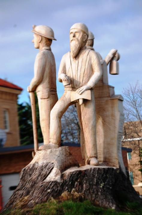 Wood Carving of Iron Workers in front of station in Ironwood, MI by Potlicker Sclupture