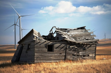 An old cabin falls apart in the midst of the giant wind turbines of the Glacier Wind Farm near Shelby, Montana
