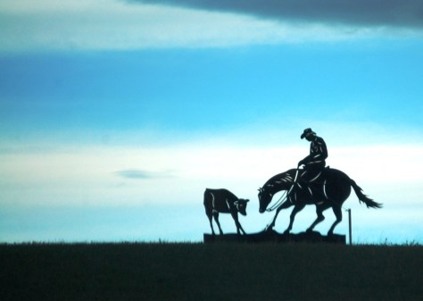 A metal cowboy sculpture on a hill south of Choteau, Montana is silhouetted against the morning sky.