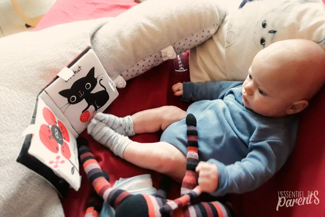 Bébé de 2 mois devant son livre d'éveil avec son doudou