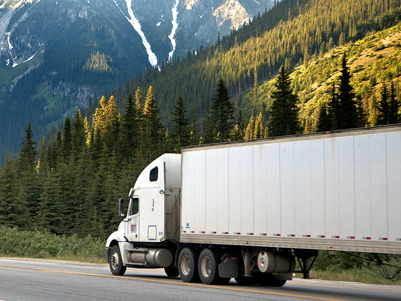 semi truck for a third party delivery service drives along a road to deliver parcels and packages