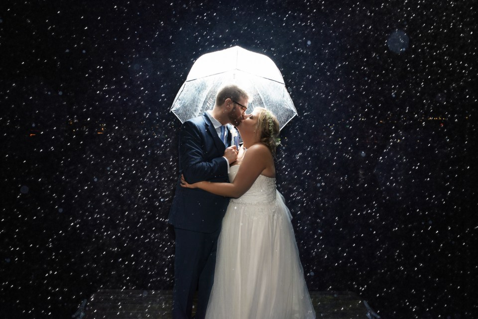 Bride & Groom in rain kissing