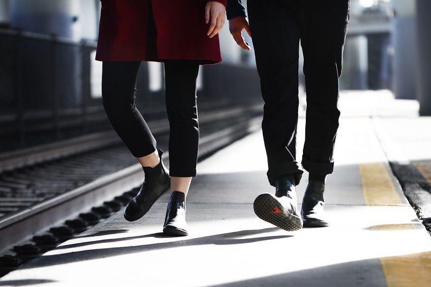 Stylish couple walking along train tracks