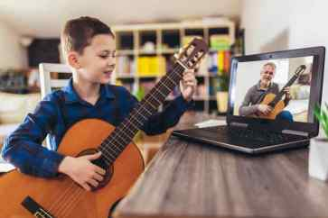 Happy little boy learning to play guitar while watching lessons on laptop at home