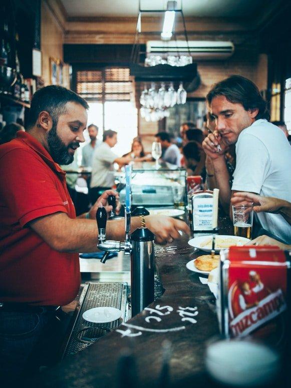 client et serveur accoudé au comptoir de las columnas à seville, voyage en espagne