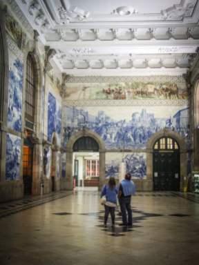 deux touristes contemplent la gare de porto et ses superbes azulejos voyage portugal