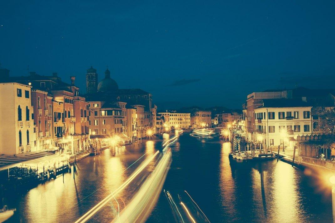 le grand canal et ses bateaux illuminé la nuit à venise en italie