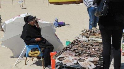 Mamy portugaise vendant de la morue séchée (remarquez le mobile à l' oreille !)