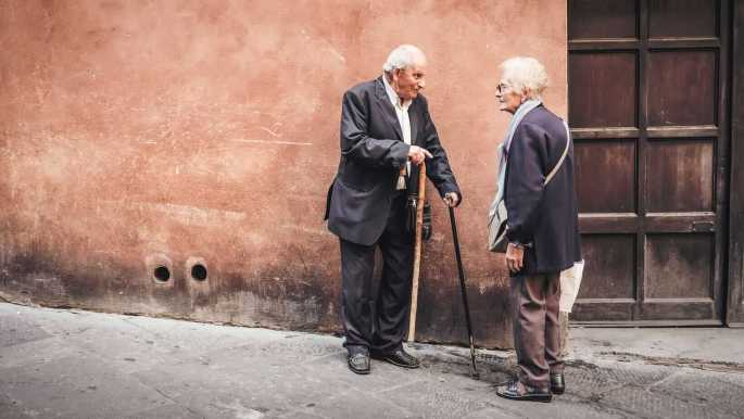 An older couple talk in the street