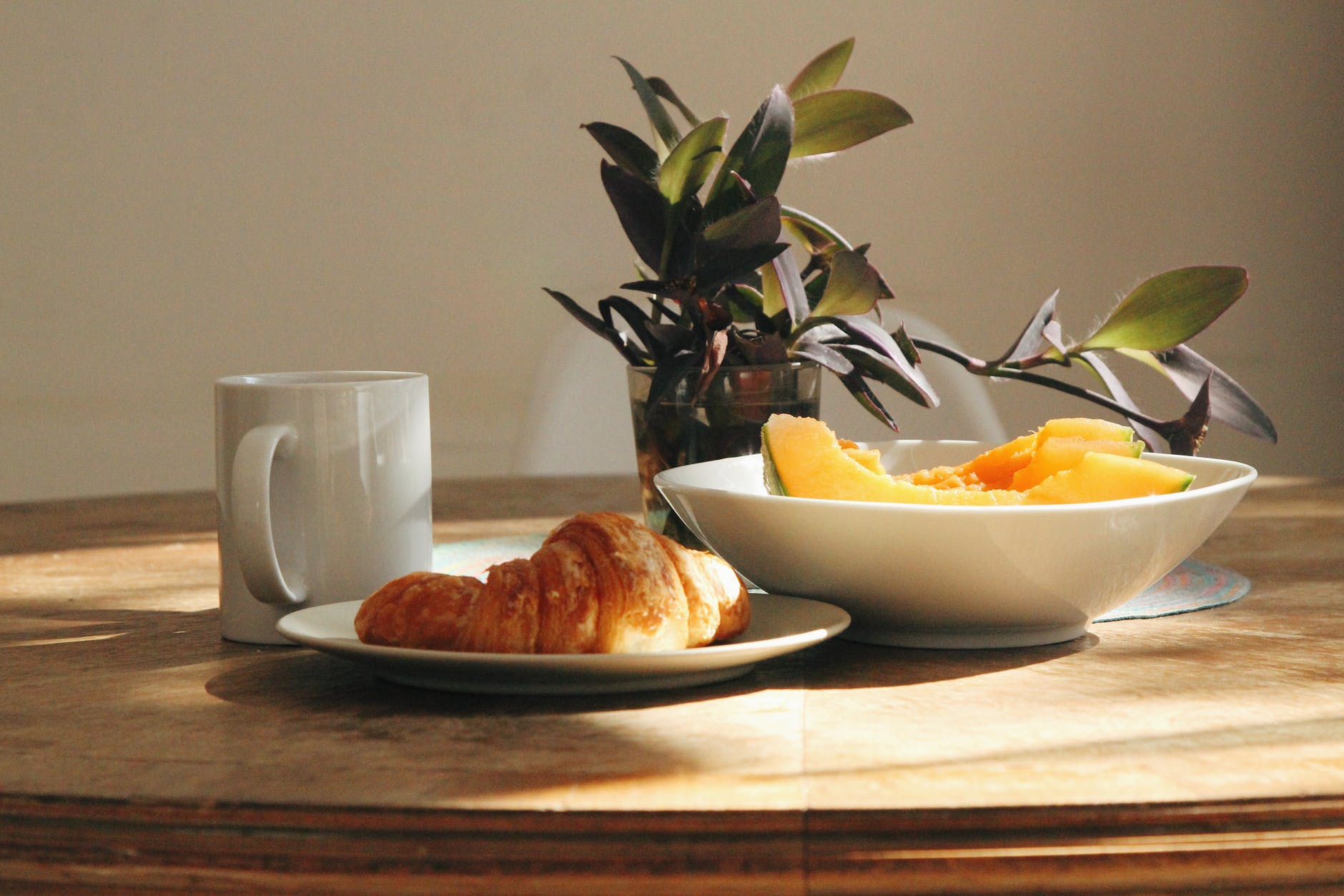 fresh fruit and croissant on wooden table