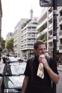 Eric eating a sandwich on the streets of Paris France