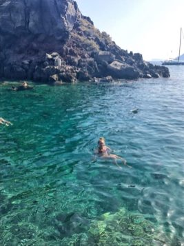Swimming in the crystal blue waters at Amoudi Bay in Santorini
