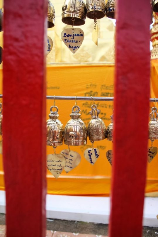 Bells with patron's names on them and Orange tapestry at Wat Phra That Doi Suthep Chiang Mai
