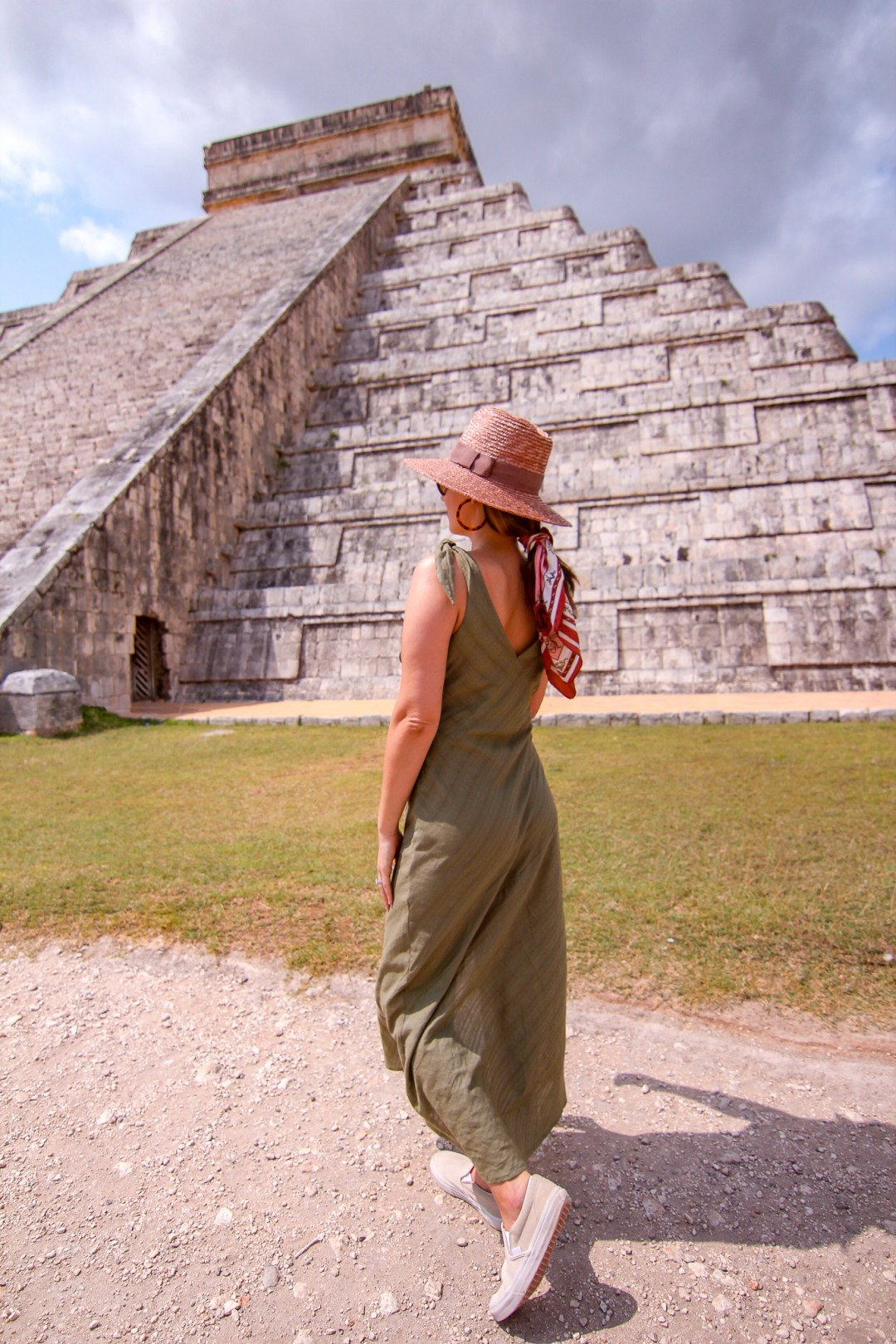 girl standing in front of chichen itza wearing a green dress and pink hat