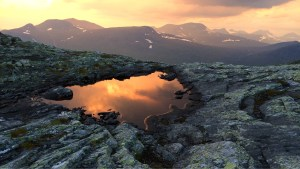 Solnedgången speglad i en vattensamling på Ruonas