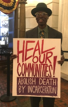 """Atilla holding """"Heal our Communities! Abolish Death by Incarceration sign"""