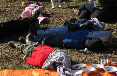 children lying on the ground with bandanas covering their faces