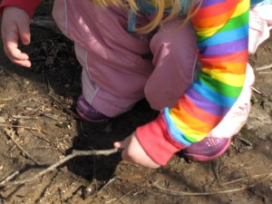 a squatting toddler pokes at mud with a stick