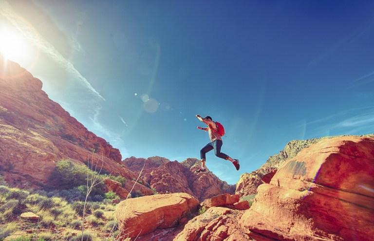 guy hiking on rocks