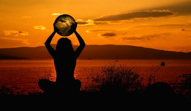lady holding globe at sunset
