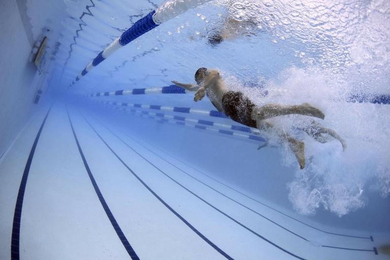 man swimming in olympic size pool