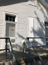 Kaia on porch in front of entrance to Meldine Schoolhouse