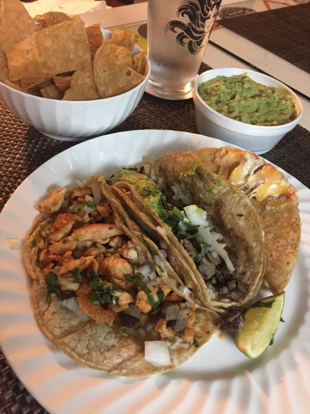 plate of tacos with a side of chips and guac