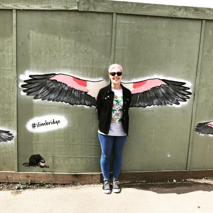 Emily the Host standing against a wall with angel wings spray painted onto it