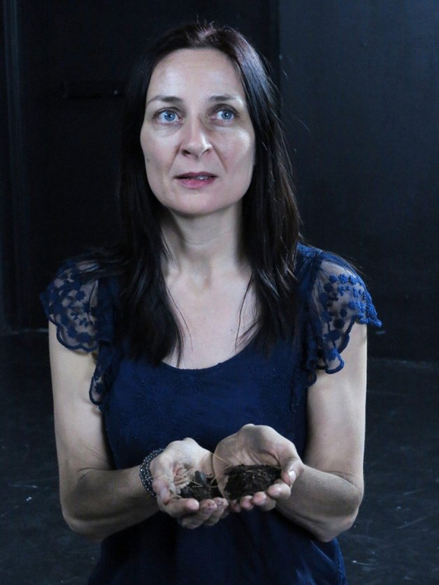 Eilin O'Dea as Antigone, holding dirt from the burial of her brother in Antigone by Jean Anouilh, presented by Fusion Theatre. Photo Jonathan Staff