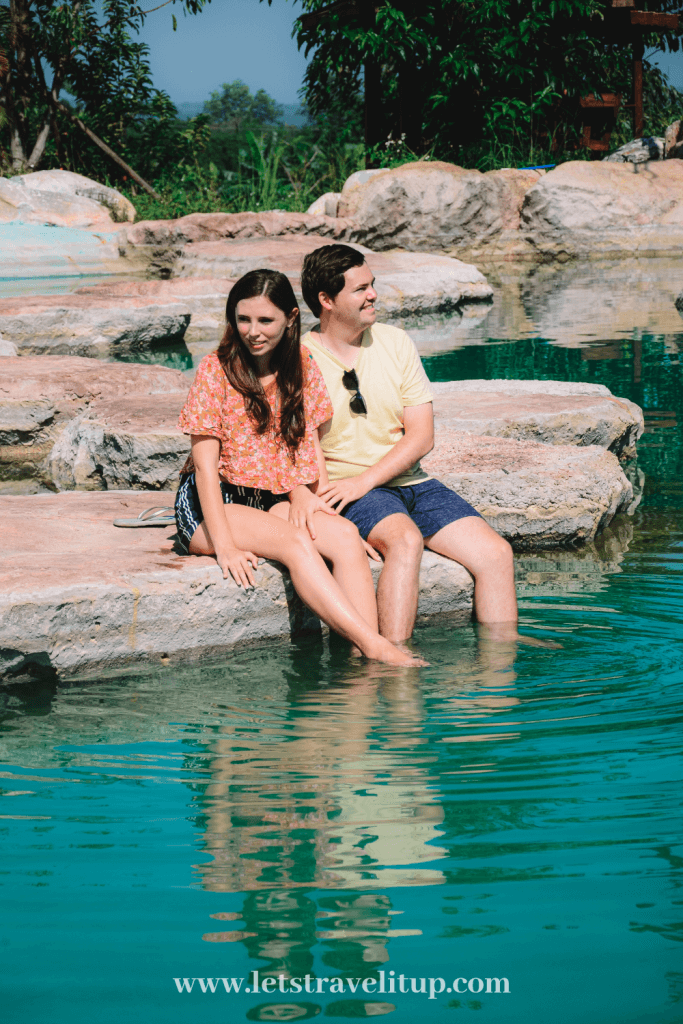 Let's Travel it up couple sitting by a beautiful pool with skipping rocks