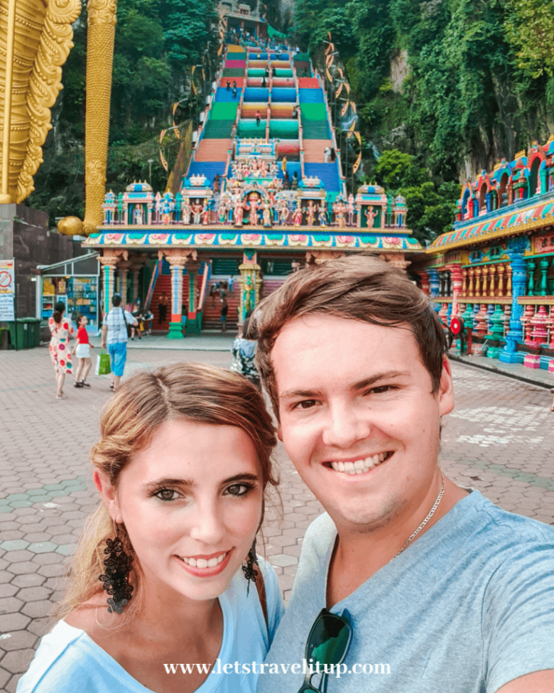 A couple posing in front of the stairs that lead up to the Batu Caves in Malaysia