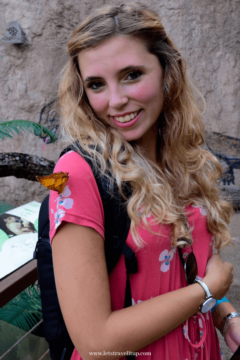 a butterfly is sitting on a girls shoulder while he visited Entopia butterfly farm on Penang Island in Malaysia