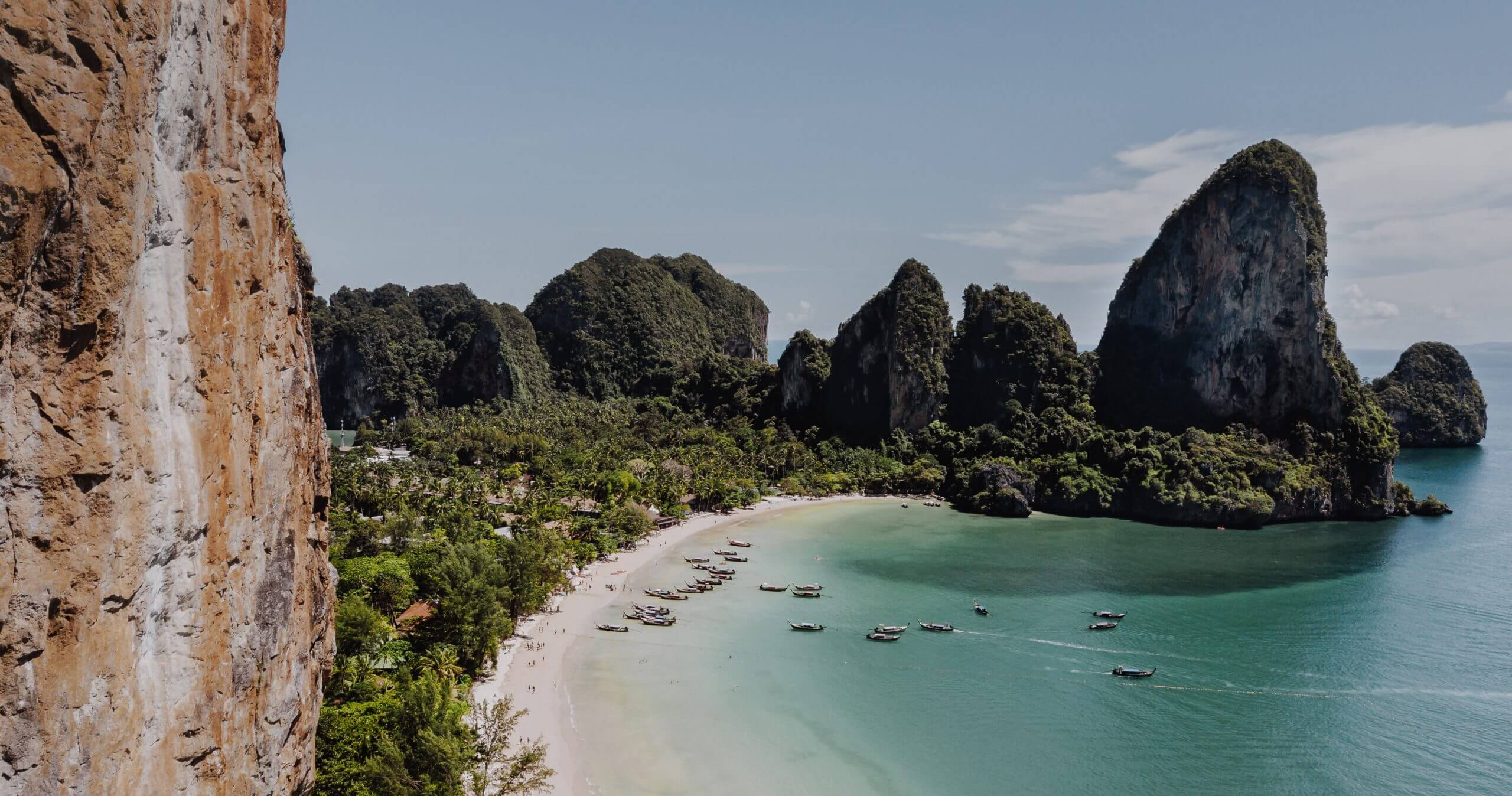 Railay beach from above with beautiful blue water and longtail boats in the water