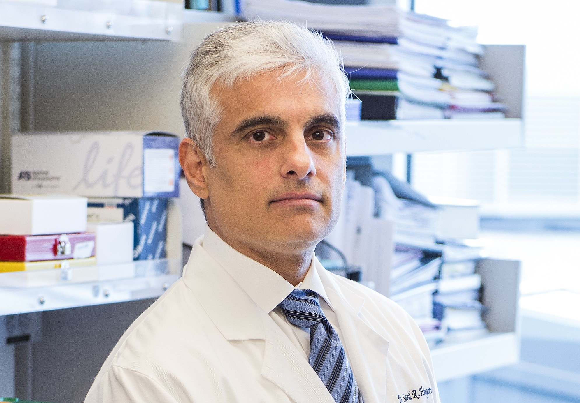 Cancer researcher Sunil Hingorani in his white coat sitting ront of office shelves