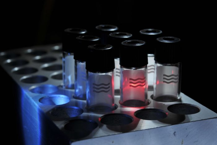clear test tubes with black caps and wavy lines on them sit upright in a solid metal rack, with red, white, and blue light shined on them