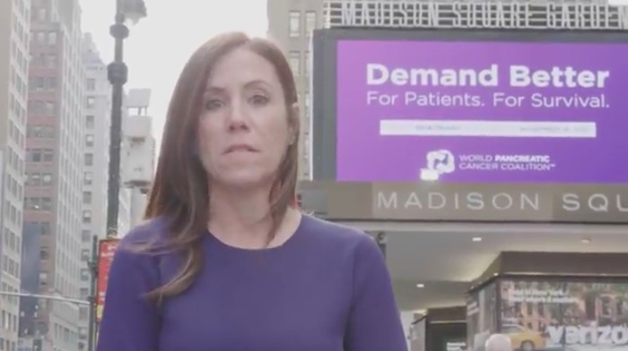Cindy Gavin of Let's Win in purple in on the street in New York City, in front of Madison Square Garden's marquee that says Demand Better, for World Pancreatic Cancer Day