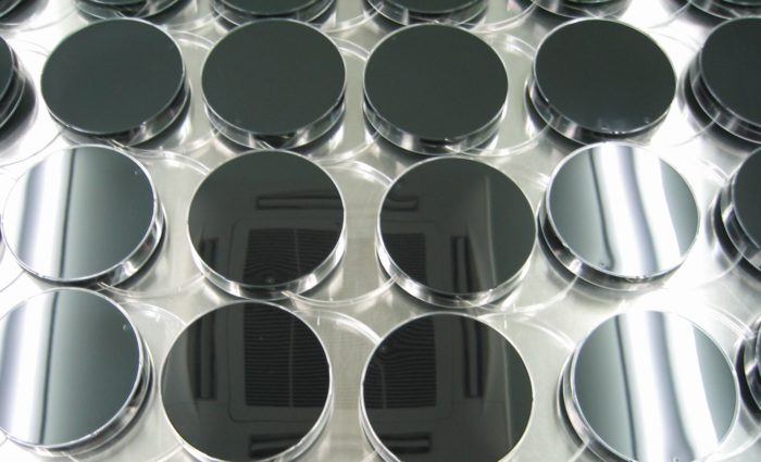 Grayscale image of round lab containers with dark agar medium arranged in rows.