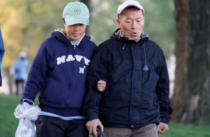 A couple in baseball caps walking for exercise