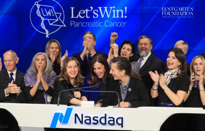 Dr. Allyson Ocean, Cindy Gavin, and Willa Shalit press the closing bell for Nasdaq to honor Pancreatic Cancer Awareness Month, surrounded by supporters. The Let's Win logo is on a blue background.