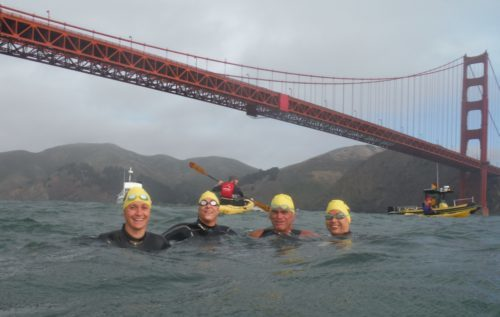 Ed Duncan and his daughters in the water below the Golden Gate Bridge as part of a cross-bay swim