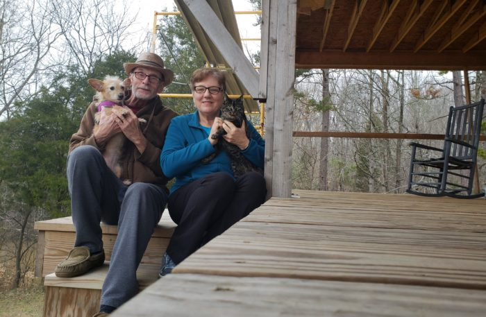 Pancreatic cancer survivor Tom Dinwiddie and his wife with their pets on the steps of a wooden porch in a rural house