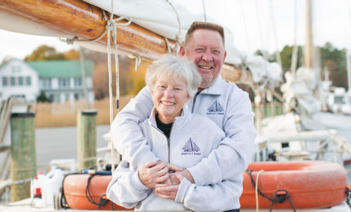 Long-term pancreatic cancer survivor Bill Shrieves and his wife Jean in front of a boat and dock
