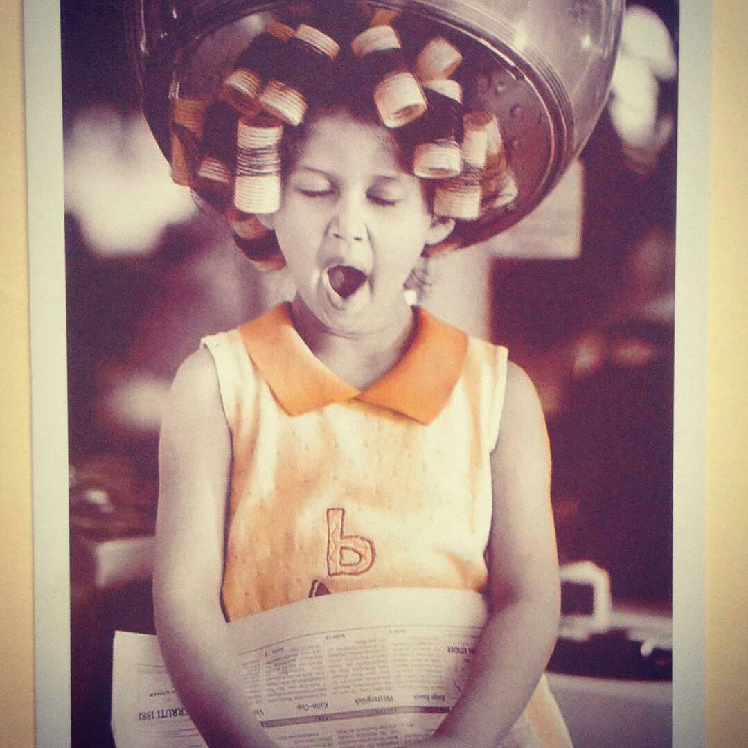 Postcard image of a young Black girl yawning with her hair in curlers under a hairdresser dryer - from @rocaduma on Instagram