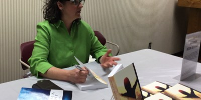 woman in green shirt signs books