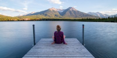 woman sitting at the edge of a dock looking at peaceful water and mountains