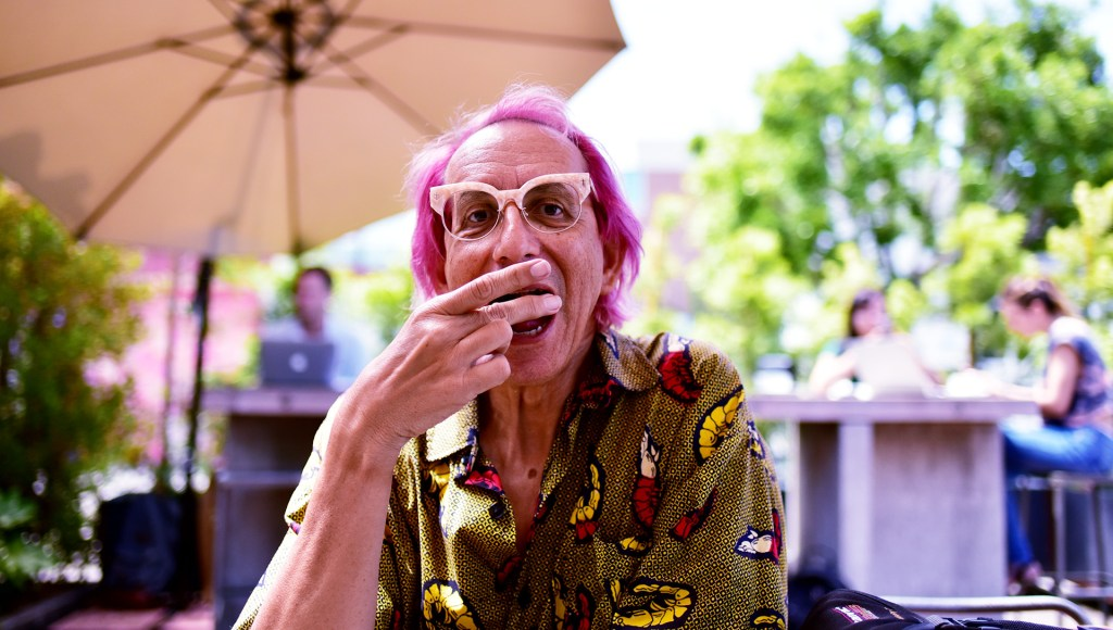 Glenn Zucman in a large shirt covered with a yellow and red shrimp print and eating a pastry at Deus Ex Machina in Venice Beach, California